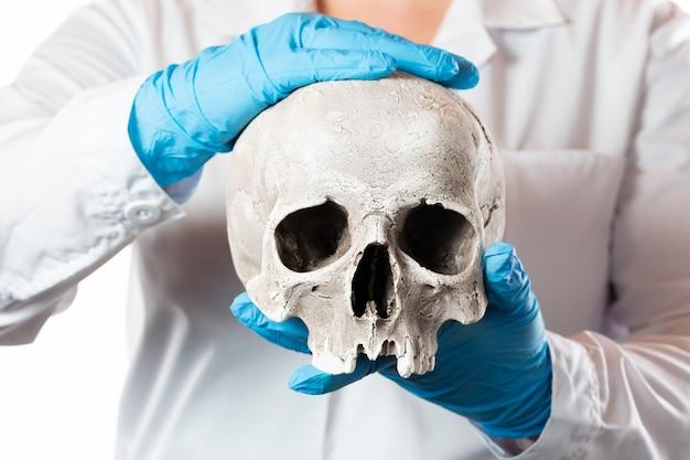 Patolog sądowy. lekarz w gumowych rękawiczkach trzyma ludzką czaszkę.