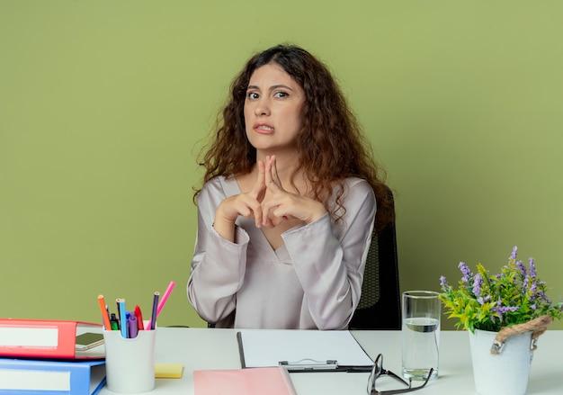 Patrz? c na aparat fotograficzny dotyczy m? odych ca? kich kobiet pracownik biurowy siedz? c przy biurku z narz? dzi biurowych, trzymaj? c si? razem za r? ce odizolowane na oliwkowym tle