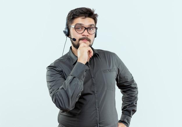 Patrz? c na aparat fotograficzny m? ody cz? owiek call center noszenie zestawu s? uchawkowego i okulary k? ad? c r? k? na brodzie wyizolowanych na bia? ym tle