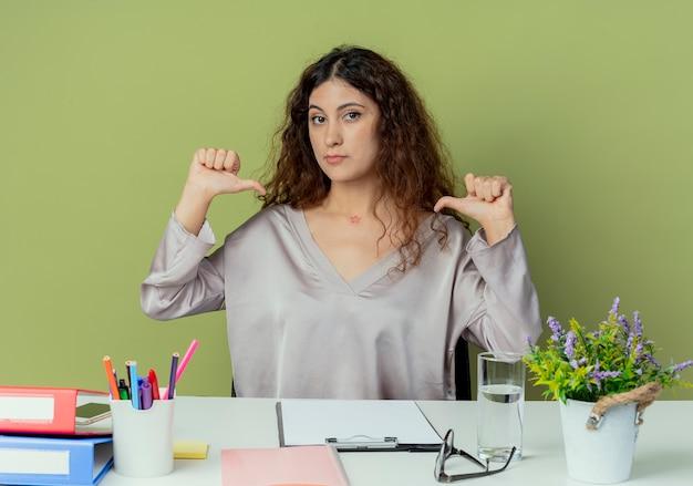 Patrz? c na aparat fotograficzny, m? odych ca? kich kobiet pracownik biurowy siedzi przy biurku z narz? dzi biurowych wskazuje na siebie odizolowane na oliwkowym tle