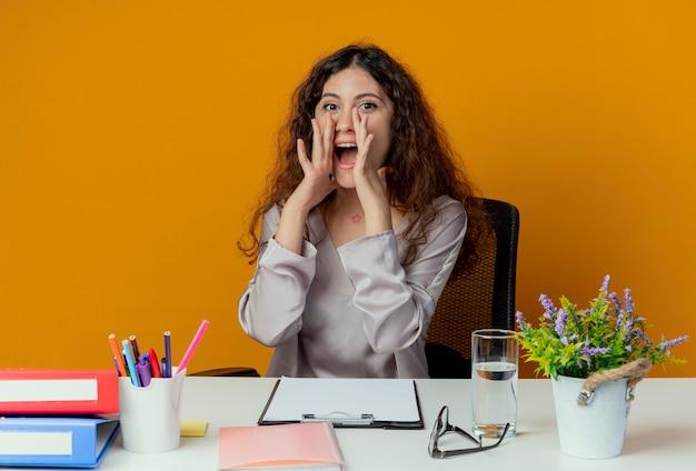 Patrz? c na aparat fotograficzny pracownik biurowy młodych całkiem żeński siedzi przy biurku z narzędzi biurowych dzwoniąc do kogoś na białym tle na pomarańczowym tle