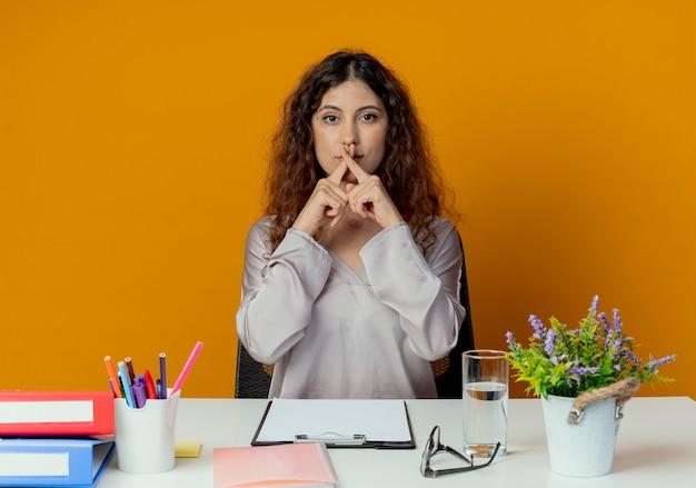 Patrz? c na aparat fotograficzny pracownik biurowy młodych całkiem żeński siedzi przy biurku z narzędzi biurowych, pokazując gest nie samodzielnie na pomarańczowym tle