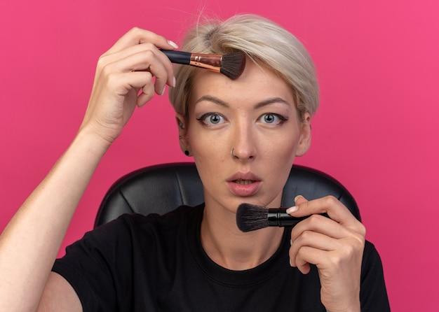 Patrząc młoda piękna dziewczyna siedzi przy stole z narzędziami do makijażu, stosując rumieniec w proszku za pomocą pędzla do pudru izolowane na różowej ścianie