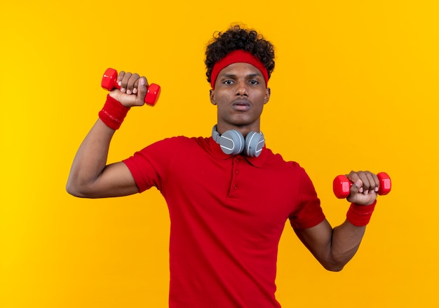 Patrząc młody afro-amerykański sportowy mężczyzna nosi opaskę i opaskę ze słuchawkami na szyi, ćwicząc z hantlami