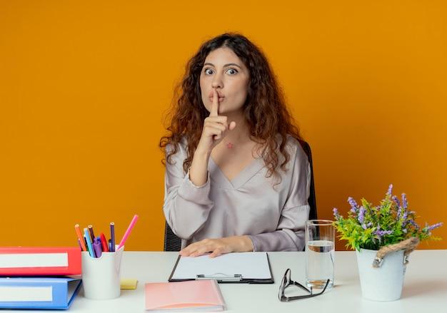 Patrząc na aparat fotograficzny ścisłe młode ładne pracownik biurowy żeński siedzi przy biurku z narzędzi biurowych pokazując gest ciszy na białym tle na pomarańczowym tle