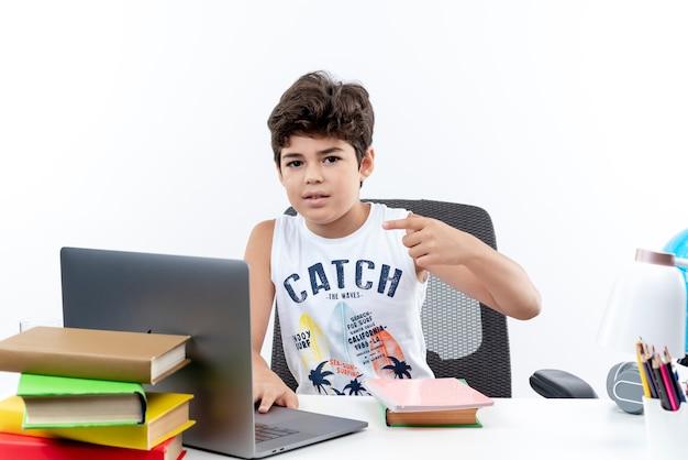 Patrząc na aparat mały uczeń siedzi przy biurku z punktami narzędzi szkolnych po stronie na białym tle na białym tle z miejsca kopiowania