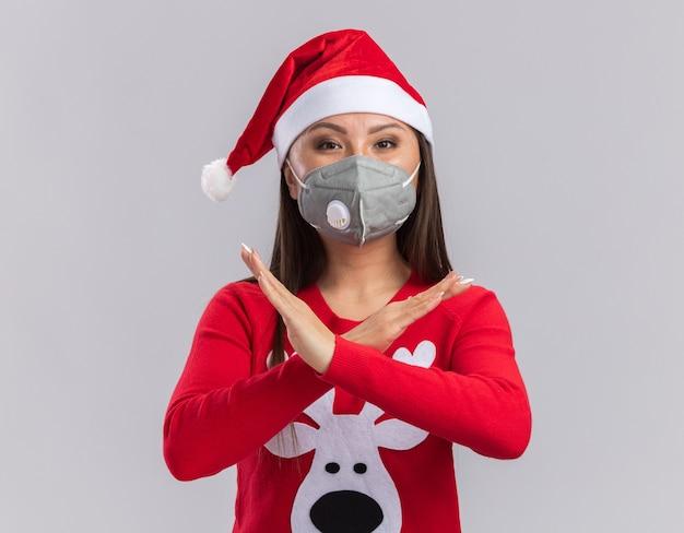 Patrząc na aparat młoda azjatykcia dziewczyna ubrana w świąteczny kapelusz ze swetrem i maską medyczną pokazując gest nie na białym tle