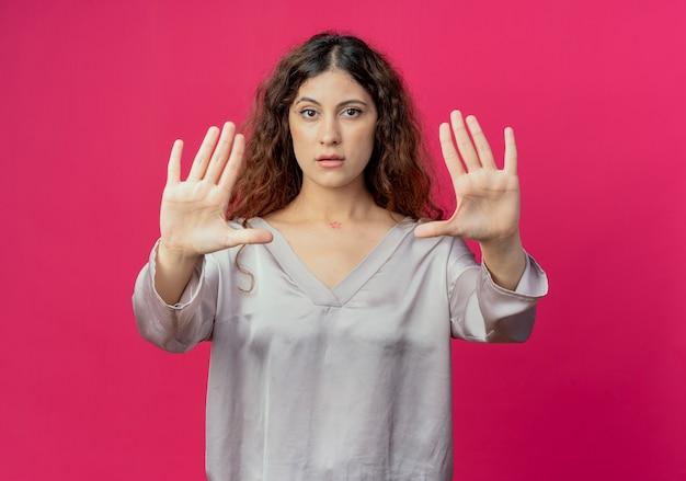 Patrząc na aparat młoda ładna dziewczyna pokazuje gest stop na białym tle na różowym tle