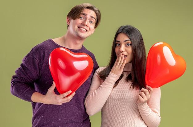 Patrząc na aparat młoda para na walentynki trzymając balony w kształcie serca na oliwkowym zielonym tle