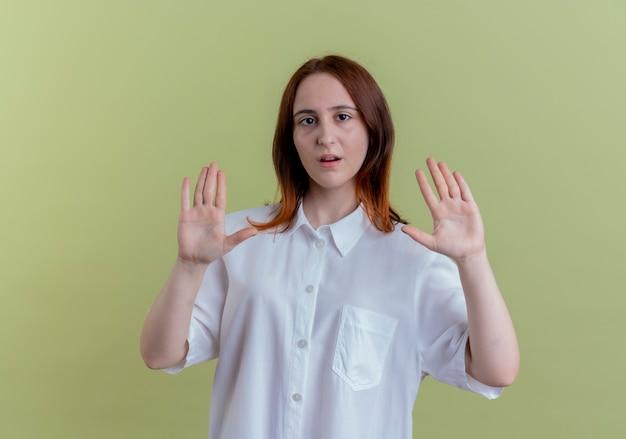 Patrząc na aparat młoda ruda dziewczyna pokazuje gest stopu na białym tle na oliwkowym tle