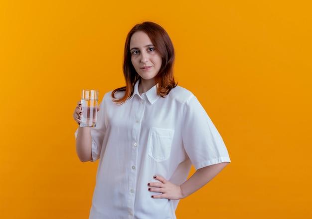 Patrząc na aparat młoda ruda dziewczyna trzyma szklankę wody i kładzie rękę na biodrze na białym tle na żółtym tle