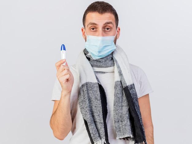 Patrząc na aparat młody chory człowiek ubrany w maskę medyczną i szalik trzyma termometr na białym tle