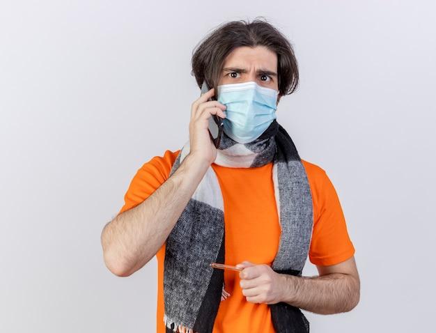 Patrząc na aparat młody chory człowiek ubrany w szalik i maskę medyczną mówi na telefon trzymając termometr na białym tle