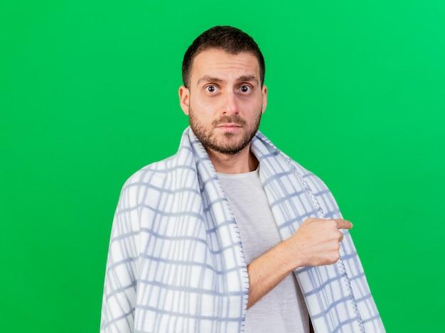 Patrząc na aparat młody chory człowiek zawinięty w kratę i wskazuje na plecy na białym tle na zielonym tle