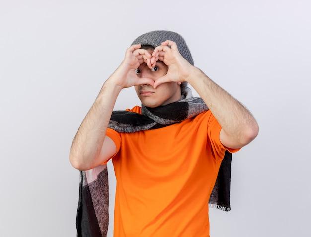 Patrząc na aparat młody chory w czapkę zimową z szalikiem pokazując gest serca na białym tle