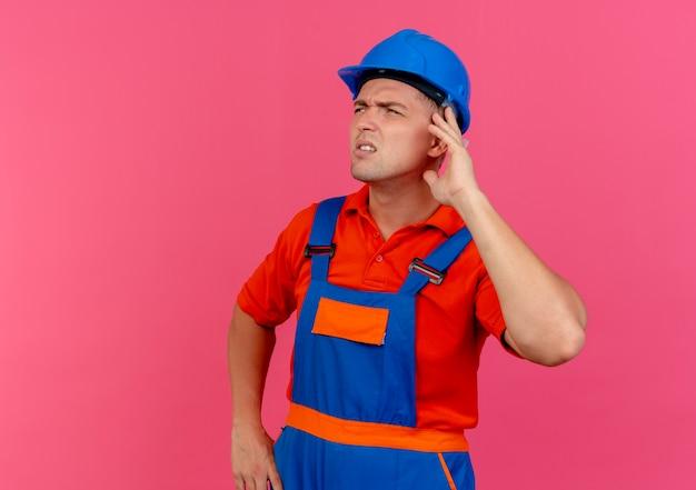 Patrząc na boczne myślenie młody mężczyzna budowniczy w mundurze i hełmie ochronnym, kładąc rękę na uchu