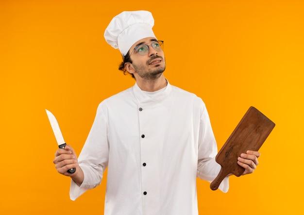 Patrząc na boczne myślenie młody mężczyzna kucharz ubrany w mundur szefa kuchni i okulary, trzymając deskę do krojenia i nóż