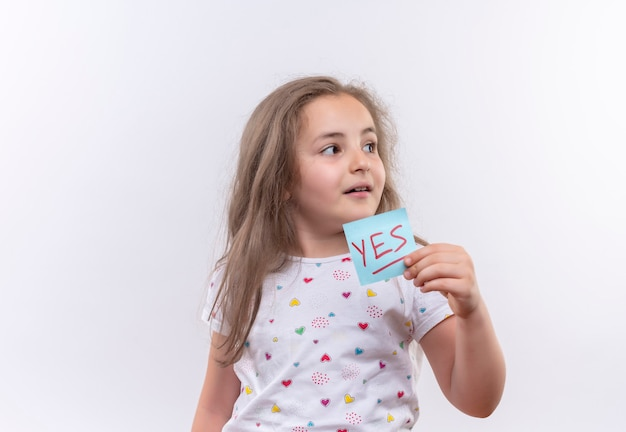 Patrząc na bok mała uczennica ubrana w białą koszulkę trzymająca papierowy znak na odizolowanej białej ścianie