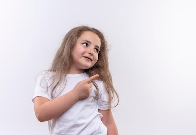 Patrząc na bok mała uczennica ubrana w białą koszulkę wskazuje na bok na odosobnionej białej ścianie