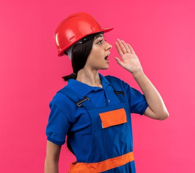 Patrząc na bok młoda budowniczy kobieta w mundurze dzwoni do kogoś
