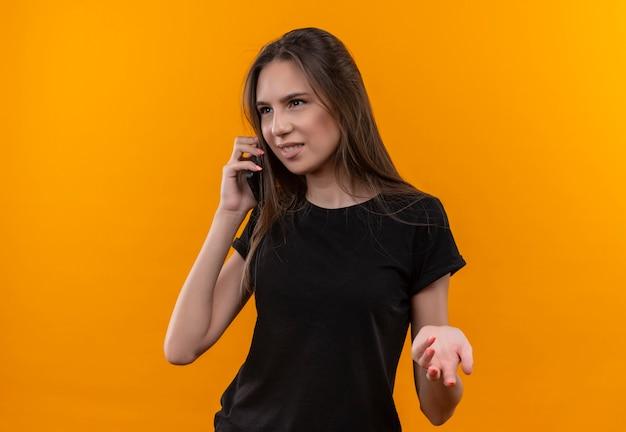 Patrząc na bok młoda dziewczyna kaukaska ubrana w czarną koszulkę rozmawia przez telefon na na białym tle pomarańczowym tle