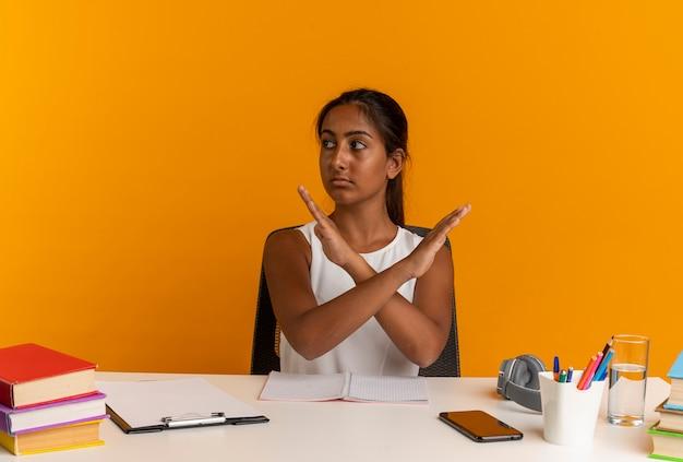 Patrząc na bok młoda uczennica siedzi przy biurku z narzędziami szkolnymi, pokazując gest nr