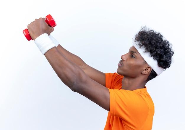 Patrząc na bok młody afro-amerykanin wysportowany mężczyzna noszący opaskę na głowę i nadgarstek trzymający hantle na bok