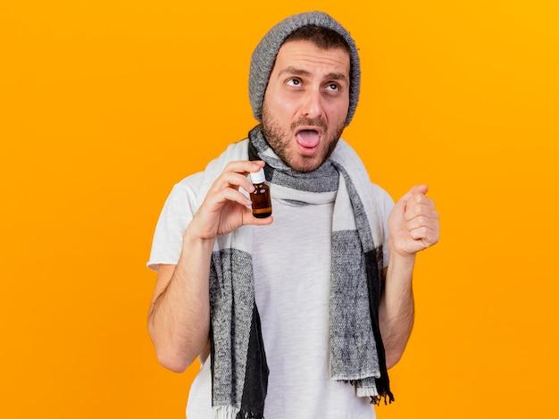 Patrząc na bok młody chory człowiek ubrany w czapkę zimową i szalik trzymając lekarstwa w szklanej butelce na białym tle na żółtym tle