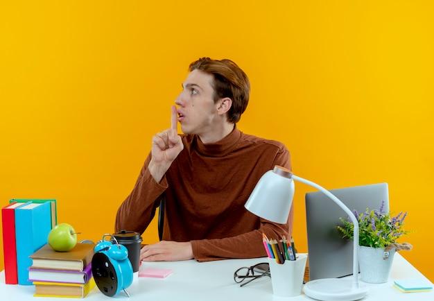 Patrząc na bok młody uczeń chłopiec siedzi przy biurku z narzędzi szkolnych pokazując gest ciszy