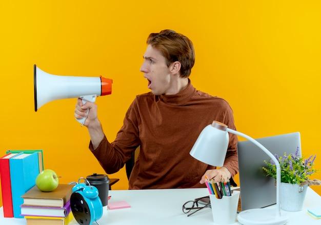 Patrząc na bok młody uczeń chłopiec siedzi przy biurku z narzędziami szkolnymi mówi na głośniku