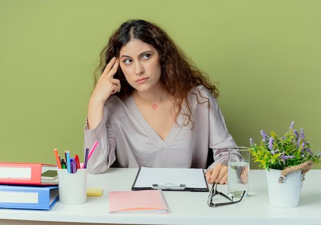 Patrząc na bok myślenie pracownik biurowy młodych całkiem żeński siedzi przy biurku z narzędzi biurowych, kładąc palec na czole na białym tle oliwek