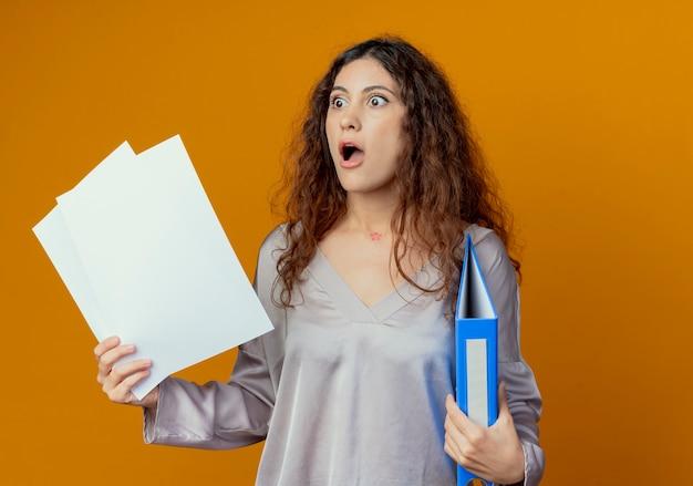 Patrząc na bok przestraszona młoda ładna dziewczyna trzyma folder i dokumenty