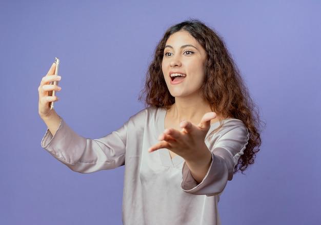Patrząc na bok radosna młoda ładna dziewczyna trzyma telefon i wyciąga rękę na białym tle na niebieskiej ścianie