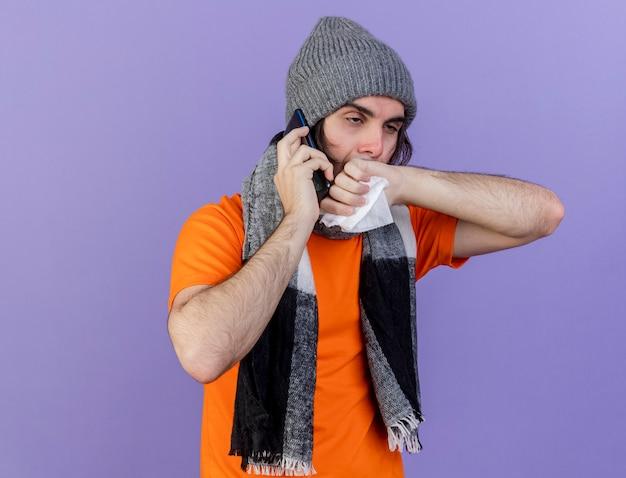 Patrząc na bok, słaby młody chory mężczyzna w czapce zimowej z szalikiem mówi przez telefon trzymając serwetkę i wycierając nos ręką odizolowaną na fioletowym tle