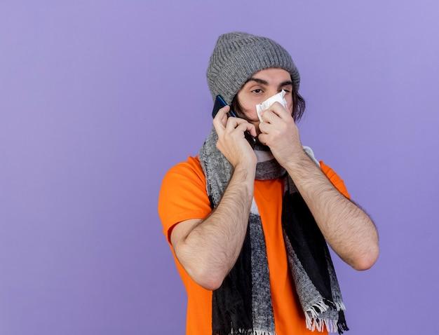 Patrząc na bok, słaby młody chory mężczyzna w czapce zimowej z szalikiem mówi przez telefon wycierając nos serwetką na białym tle na fioletowym tle