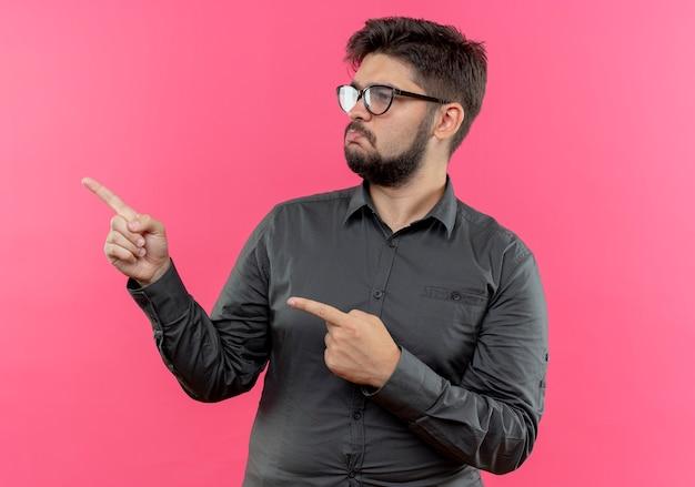Patrząc na bok smutny młody biznesmen w okularach wskazuje na bok na białym tle na różowej ścianie z miejsca na kopię