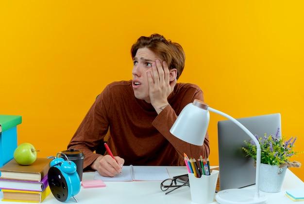 Patrząc na bok smutny młody uczeń chłopiec siedzi przy biurku z narzędziami szkolnymi, kładąc rękę na policzku