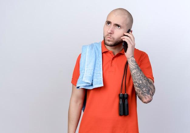 Patrząc na bok, surowy młody sportowy mężczyzna rozmawia przez telefon z ręcznikiem i skacze przez skakankę na ramieniu