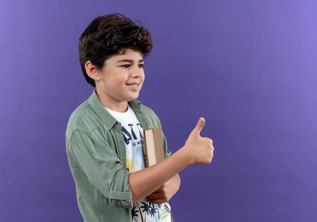 Patrząc na bok uśmiechnięty mały uczeń trzyma książkę kciuk w górę