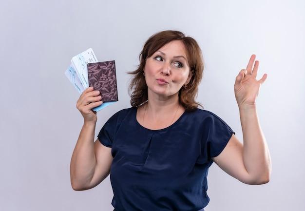 Patrząc na bok, zadowolona podróżniczka w średnim wieku trzymająca bilety i portfel pokazująca gest okey na odizolowanej białej ścianie