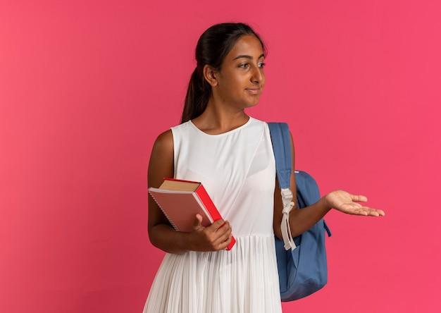 Patrząc na bok, zadowolony młoda uczennica w plecaku, trzymając książkę z notatnikiem i wskazuje ręką na boku