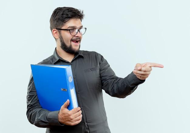 Patrząc na bok zadowolony młody biznesmen w okularach, trzymając folder i wskazuje na bok