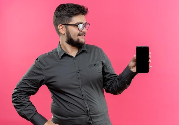 Patrząc na bok zadowolony młody biznesmen w okularach, trzymając telefon na bok na białym tle na różowej ścianie
