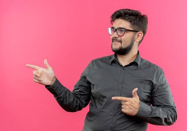 Patrząc na bok zadowolony młody biznesmen w okularach wskazuje na bok