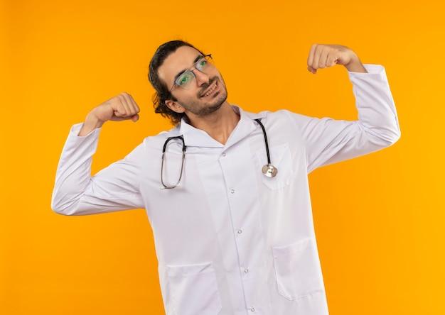 Patrząc na bok zadowolony młody lekarz w okularach medycznych ubrany w szlafrok medyczny ze stetoskopem pokazujący silny gest