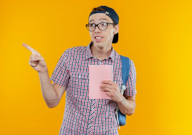 Patrząc na bok, zadowolony młody uczeń w plecaku, okularach i czapce trzymającej notatnik i wskazuje na bok