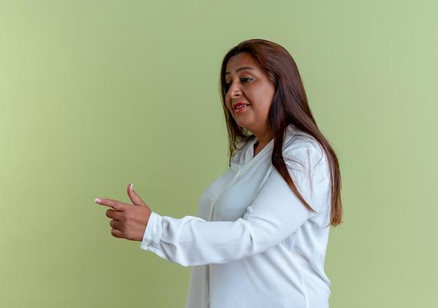 Patrząc na bok zadowolony, przypadkowa kaukaska kobieta w średnim wieku wskazuje na bok