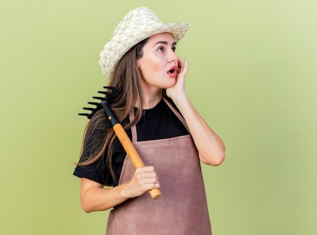 Patrząc na bok, zaskoczona piękna ogrodniczka w mundurze w kapeluszu ogrodniczym trzymająca grabie na ramieniu kładąca dłoń na policzku odizolowana na oliwkowym tle