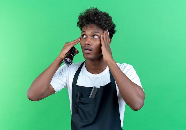 Patrząc na bok zaskoczony młody afroamerykański męski fryzjer ubrany w mundur trzymający maszynkę do strzyżenia włosów i kładący ręce na czole
