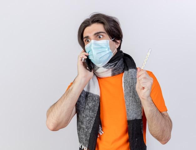 Patrząc na bok, zaskoczony młody chory człowiek ubrany w szalik i maskę medyczną mówi przez telefon i trzyma termometr na białym tle